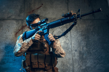 American private military contractor holding rifle. Image on a dark background