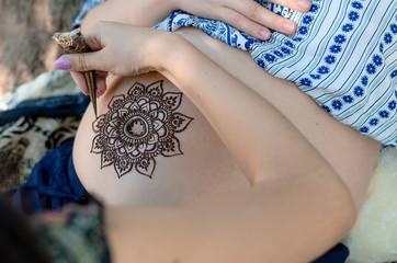 Master is drawing henna tatto on pregnant belly, closeup.  A mehendi artist paints a beautiful mandala. Motherhood concept, happy maternity