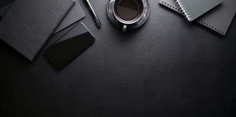 Dark trendy workplace with smartphone and office supplies on black leather table background