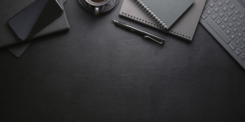 Top view of dark stylish workplace with smartphone and office supplies