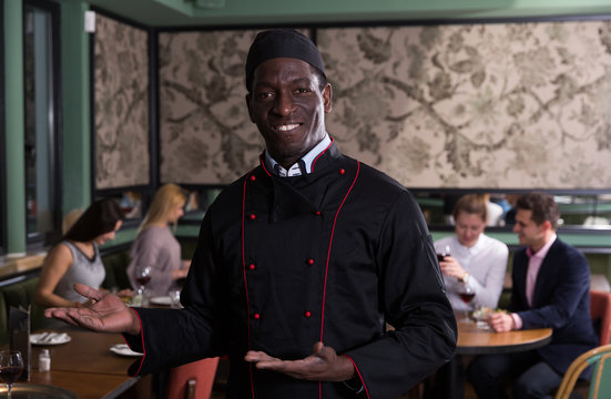 Smiling African American chef inviting to restaurant
