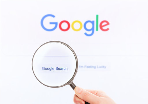 Google homepage on the screen under a magnifying glass. Google is world's most popular search engine. Moscow, Russia - April 27, 2019