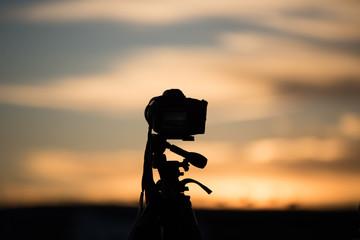 夕焼けに向かうカメラのシルエット