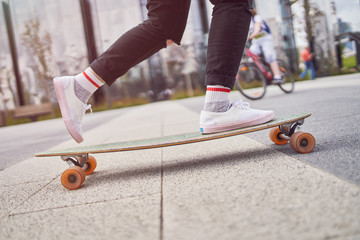 Picture of legs of woman in black jeans riding skateboard on street in city