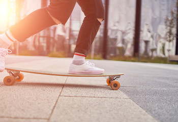 Picture of woman's legs in white sneakers riding skateboard on street in city on summer day.