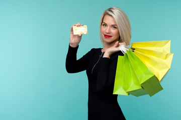 Image of a beautiful happy young blonde woman posing isolated over blue wall background holding shopping bags.