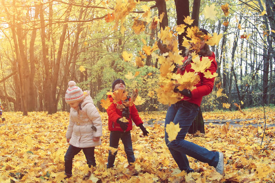happy family walking in sunny park and throws orange maple leaves. mother with kids enjoying autumn weather outdoors