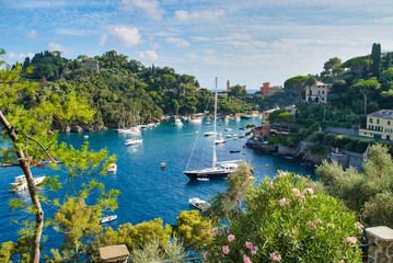 Portofino, Italy - AUGUST 15, 2019: Beautiful harbor in the Italian Riviera, houses on a cliff, boats and a yacht on water / a popular resort in Europe