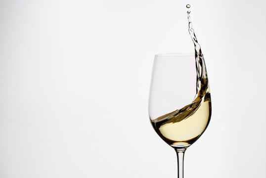 White wine splashing from an elegant wineglass