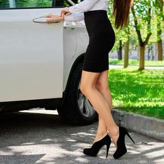 Unrecognizable girl opens the door of her car