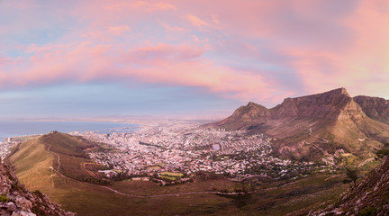 Moody Table Mountain after sunset with city lights as seen from Lions Head.