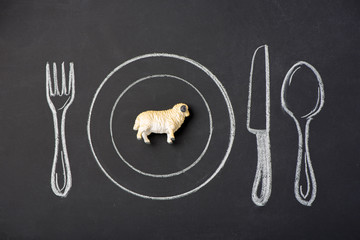 Toy sheep on a plate in the figure on the chalk board