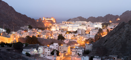 Old Muscat buildings after sunset with a view over Al Jalai Fort, middle east, Oman.
