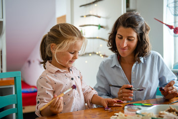 Mother and daughter painting Christmass ornaments