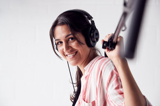 Portrait Of Female Sound Recordist Holding Microphone On Video Film Production In White Studio