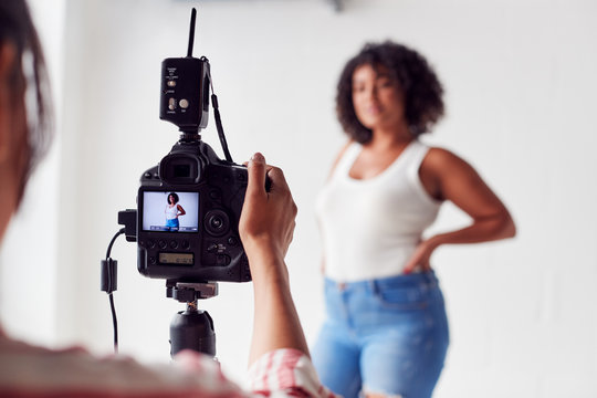 Female Photographer In Digital Studio Shooting Images On Camera Tethered To Laptop Computer