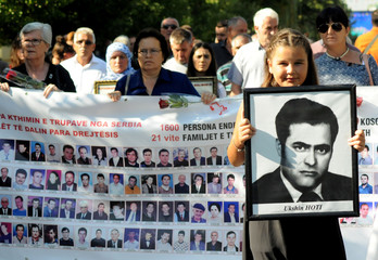A girl holds a picture of a missing person to mark The International Day of the Disappeared in Pristina