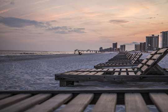 Relaxing wood beach chairs lined up in Orange Beach, Alabama ready for vacation