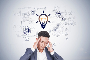Stressed Asian man thinking about formulas