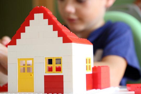 Junge baut mit Bausteinen ein Wohnhaus
