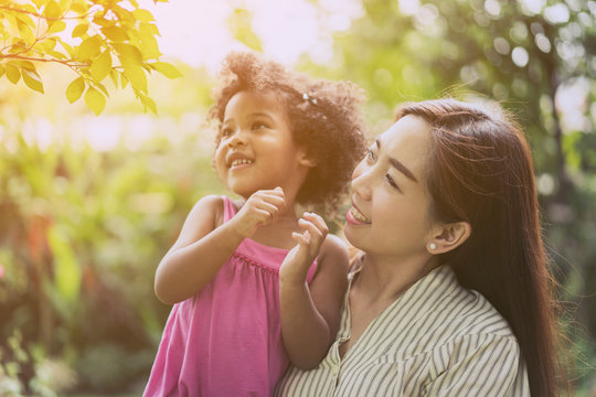 Cute young daughter with her Asian parent or Child care staff relaxing and enjoying in nature on outdoor. Mother with her 5 years old kids playing together in a park. Mother day. family, life concept