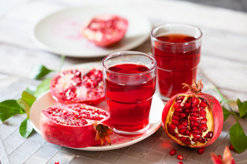Pomegranate juice with fresh pomegranate fruits on wooden table