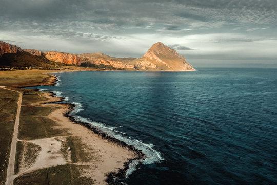 Luftaufnahme eines Strandes auf Sizilien mit einem Berg im Hindergrund