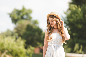 Wall Mural - beautiful girl in white dress touching straw hat and looking down