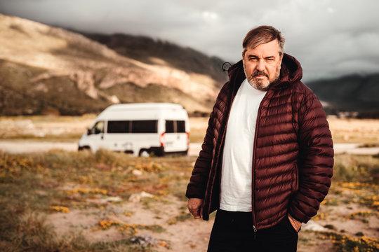 Mann mit weißem Tshirt und weinroter Jacke steht in Landschaft mit Van im Hintergrund