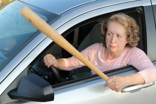 Angry mature female driver holding baseball bat