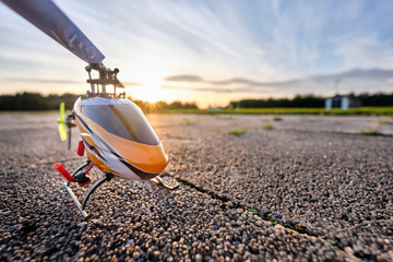 In de dag Helicopter A RC helicopter standing on the ground during sunset on a beautiful summer day
