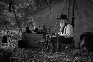 Vintage image, of a man dressed in a cowboy outfit, sitting and relaxing at his camp