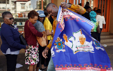 Queueing customers look on as a man unfolds a cloth with printed image of Pope Francis he bought at a store in Maputo