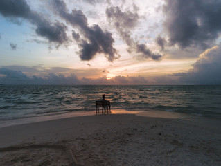 Sunset in the Maldives - A young woman is sitting on a bench while looking at the sea