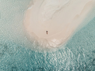 Aerial view of a sandbank in the Maldives sea - A young woman is lying on the white sand while looking at the sea