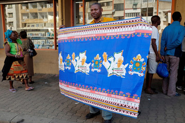 A man poses with a cloth with printed images of Pope Francis he bought at a store in Maputo