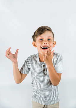 Little boy with autism standing on a white background feeling happy and smiling with his arms raised