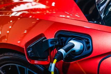 Red EV Car at charging station with the power cable supply plugged in. Power supply connect to electric vehicle for charging the battery.