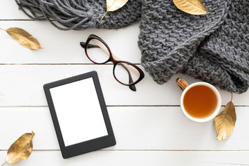 Autumn composition. Feminine desk table with knitted scarf, tea cup, glasses, tablet ebook with blank screen, fall leaves on wooden background. Flat lay, top view. Nordic, hygge, cozy home concept
