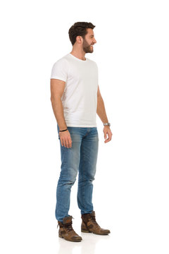 Handsome Man In Jeans And White T-shirt Is Standing, Smiling And Looking Away. Side View.