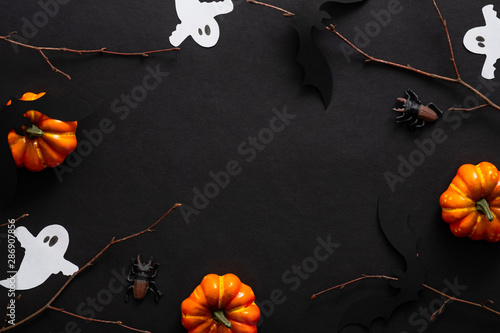 Halloween composition with ghosts, bats, pumpkins on black background. Halloween party invitation card mockup. Flat lay, top view, copy space.