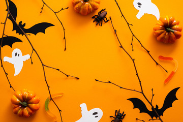 Happy halloween holiday concept. Halloween decorations, pumpkins, bats, candy, ghosts, bugs on orange background. Halloween party greeting card. Flat lay, top view, overhead. Fototapete