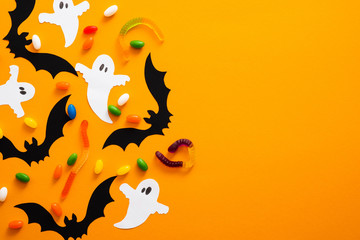 Happy halloween holiday concept. Halloween decorations, bats, ghosts, candy on orange background. Halloween party greeting card mockup with copy space. Flat lay, top view, overhead. Fototapete