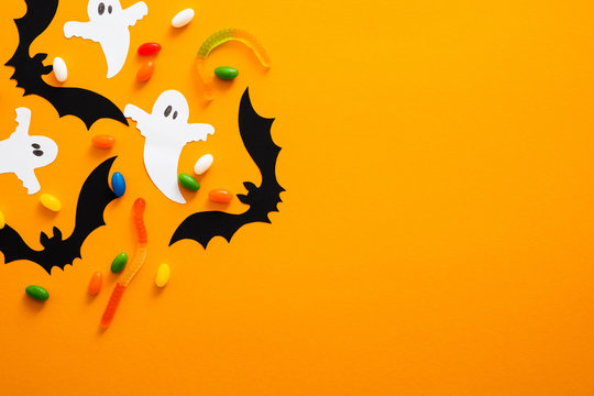 Happy halloween holiday concept. Halloween decorations, bats, ghosts, candy on orange background. Halloween party greeting card mockup with copy space. Flat lay, top view, overhead.
