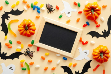 Halloween decorations, picture frame with black paper card mockup on pastel beige background. Decorative pumpkins, paper bats, spiders, candy. Halloween concept. Flat lay, top view, copy space