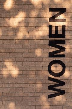 Women Restroom Sign on Brick Wall