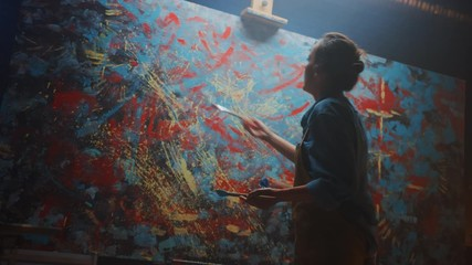 Fototapete - Talented Female Artist Energetically and Violently Using Paint Brush She Creates Modern Masterpiece of the Oil Painting. Creative Studio with Large Canvas of Striking Colors. Low and Tip Angle Shot
