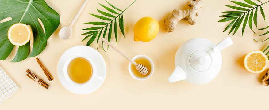 Herbal tea with mint, ginger, lemon, honey and other herbs on yellow background. Flat lay, top view.