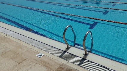 Fototapete - Grab bars ladder in the swimming pool