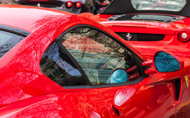 Paris,France December 11, 2011: Close-up image of Ferrari cars with autumn city reflections in a street parking